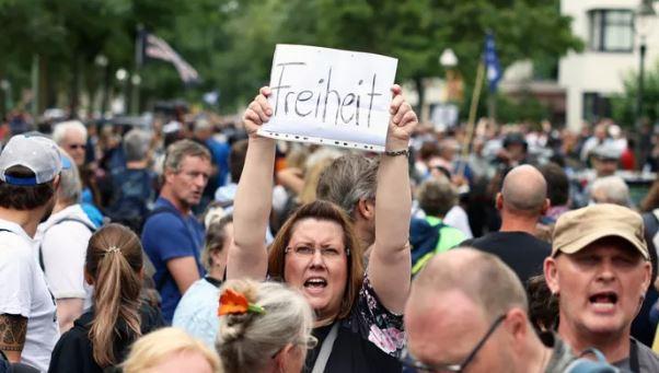 Протестующий держит плакат с надписью «Свобода» во время демонстрации против политики правительства в области здравоохранения. (иллюстрация – фото REUTERS)